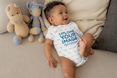Onesie Mockup of a Cute Baby Boy Lying in Bed with Stuffed Animals 25121