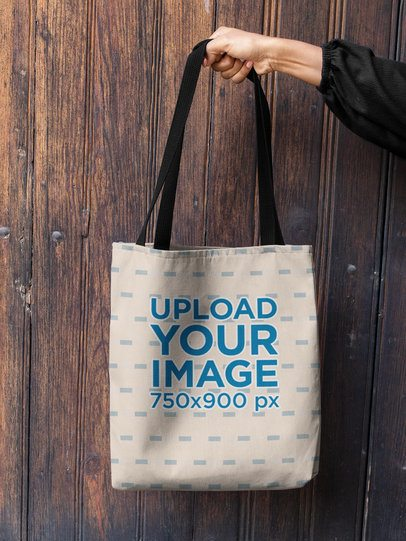 Mockup of a Woman's Hand Holding a Tote Bag Against a Wooden Background 26693