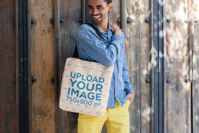 Tote Bag Mockup Featuring a Smiling Man Standing by a Wooden Door 26706