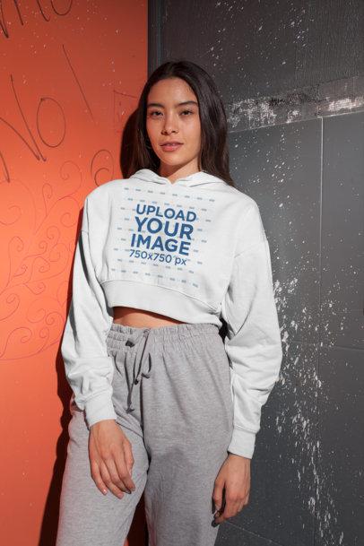 Crop Top Hoodie Mockup of a Girl in Sport Pants Against a Dirty Wall 26097