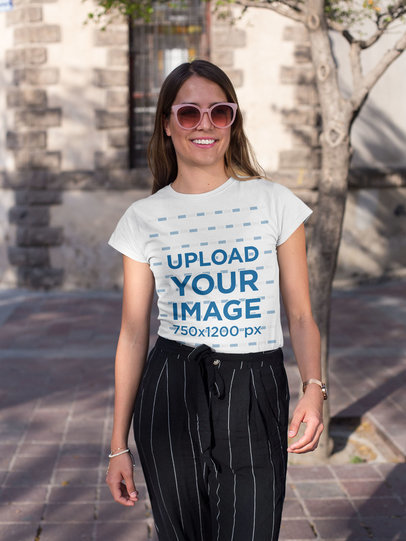 Tee Mockup of a Woman with Sunglasses Walking Around Downtown 26351