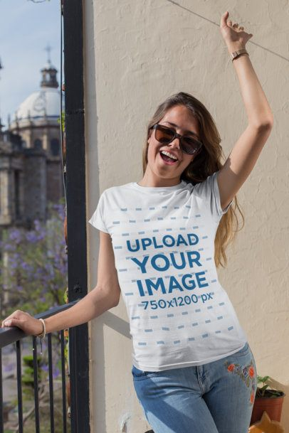 T-Shirt Mockup of a Cheerful Woman with Sunglasses Celebrating on a Balcony 26361