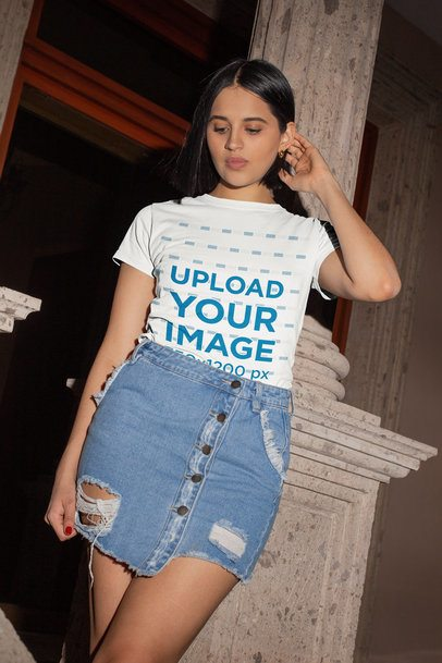 Tee Mockup of a Young Woman in a Denim Skirt Leaning over a Concrete Column 26543