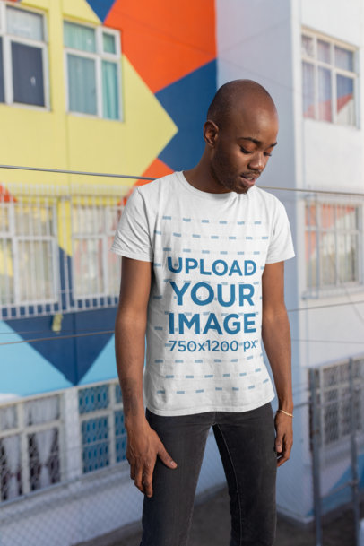 Mockup of a Man Wearing a Tee in Front of Graffiti Art 26322