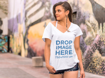 T-Shirt Mockup of a Girl Walking Past a Colorful Mural a7620