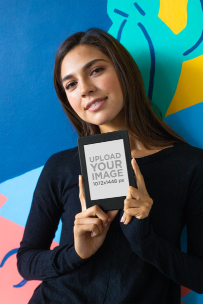 Mockup of a Cute Girl Against a Colorful Wall Holding a Kindle Paperwhite 26155