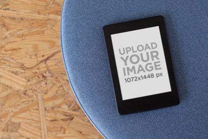Kindle Paperwhite Mockup over a Blue Cushion 26158