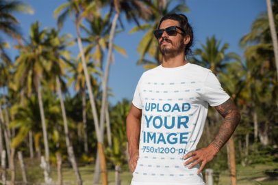 T-Shirt Mockup of a Tattooed Man Standing by Palm Trees  26759