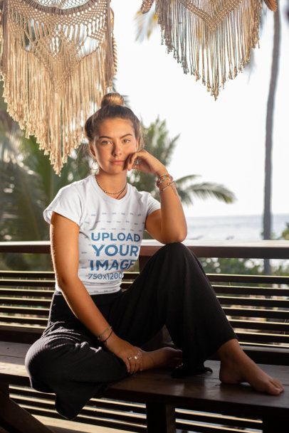 Tee Mockup of a Woman with a Hair Bun Sitting on a Bench by the Beach 26863