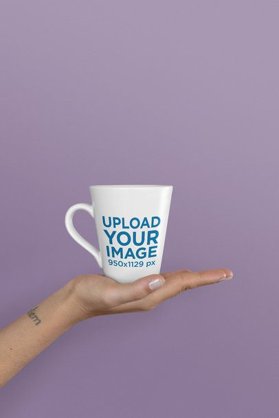 Mockup of an 11 oz Coffee Mug Held Up Against a Solid Background 26564