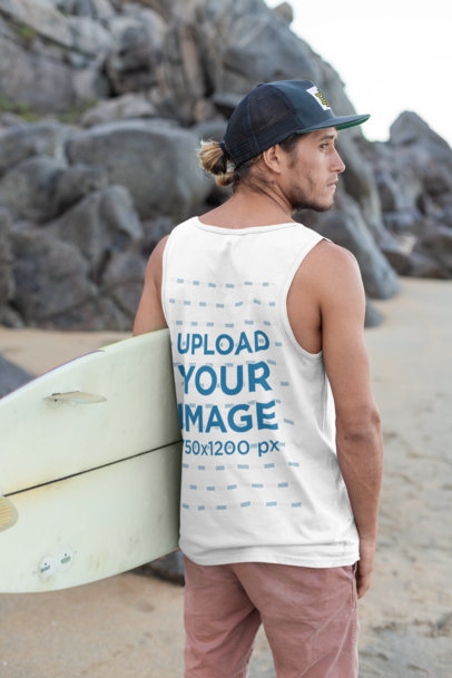 Back View Tank Top Mockup of a Young Man with a Cap Carrying a Surfboard by the Beach 26794