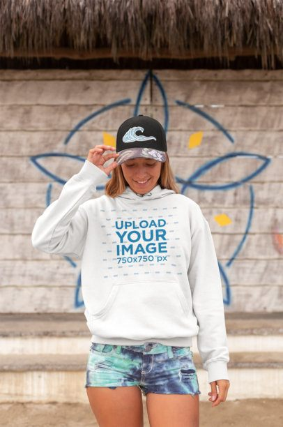 Pullover Hoodie Mockup of a Long-Haired Girl Wearing a Cap Against a Summer Wall Drawing 26811