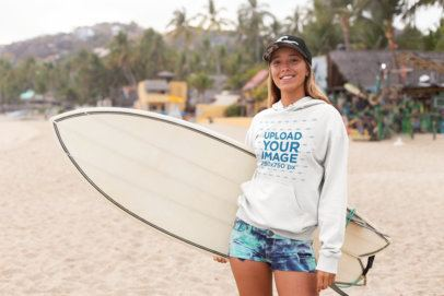 Mockup of a Cool Surfer Woman Standing on a Beach Wearing a Hoodie 26814