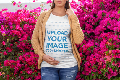 Mockup of a Pregnant Woman Wearing a T-Shirt in front of a Floral Bush 26657