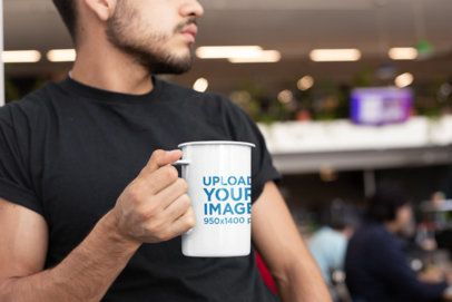Mockup of a 21 Oz Enamel Mug Held by a Young Man 26934