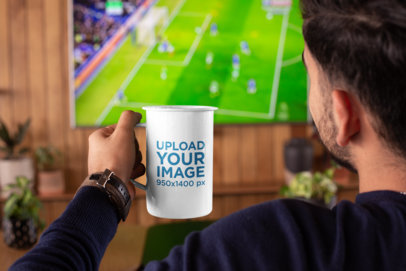 Mockup of a Man Watching a Soccer Match with a 21 oz Enamel Mug in His Hand 26939