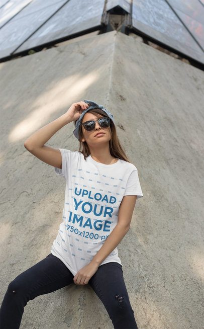 T-Shirt Mockup of a Trendy Woman with Sunglasses Leaning over a Concrete Structure 27340