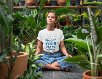 T-Shirt Mockup of a Relaxed Young Woman Sitting in a Greenhouse  27084