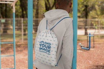 Drawstring Bag Mockup of a Man at a Park Facing Backward 27583