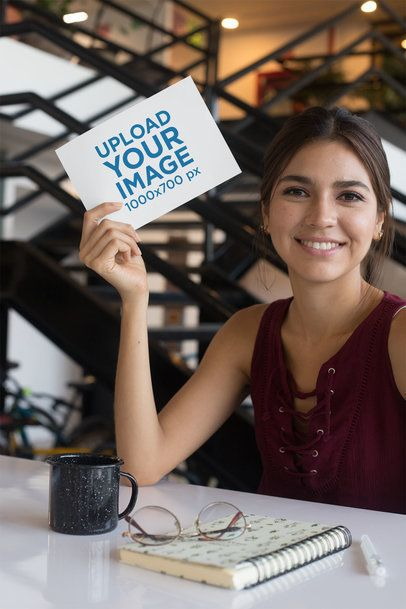 Mockup of a Smiling Woman at a Table Holding an A5 Flyer 27364