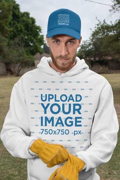 Mockup of a Male Cowboy Wearing a Pullover Hoodie and a Trucker Hat 27962