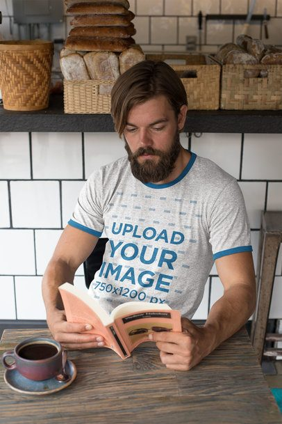 Ringer Tee Mockup Featuring a Hipster Man Reading at a Bakery 27914