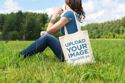 Tote Bag Mockup of a Woman Sitting at a Green Meadow 23-el