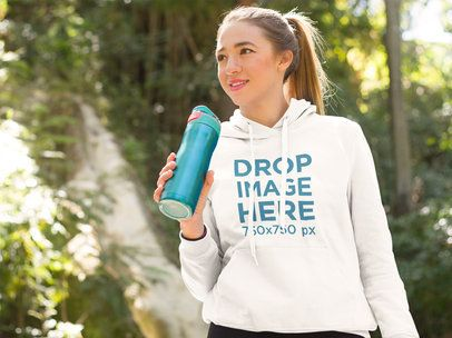 Young Woman at a Park Drinking Water Hoodie Mockup a8513