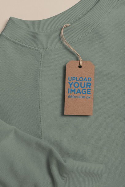 Mockup of a Cardboard Clothing Tag Lying on a Sweater 27659