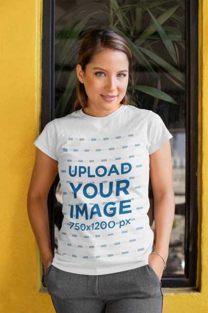 T-Shirt Mockup Featuring a Young Woman Standing in Front of a Closed Window 28209