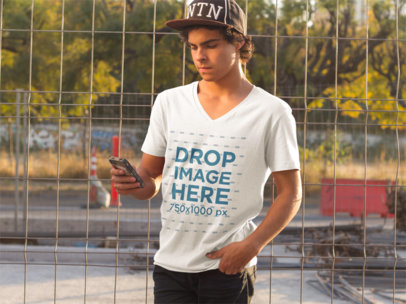 Guy at a Skate Park Using an iPhone T-Shirt Mockup a8941