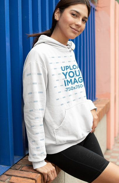 Hoodie Mockup with a Customizable Sleeve Featuring a Woman Leaning Over a Brick Wall 28301