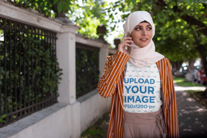T-Shirt Mockup Featuring a Woman Wearing a Hijab While Using Her Mobile 28293