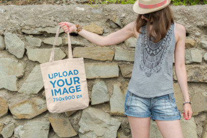 Mockup of a Woman Holding a Canvas Tote Bag Mockup Against a Rocky Wall 105-el
