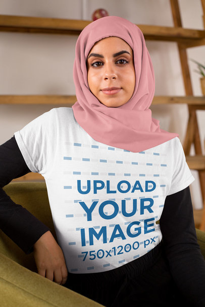 T-Shirt Mockup Featuring a Woman with a Hijab Sitting on a Sofa 28272
