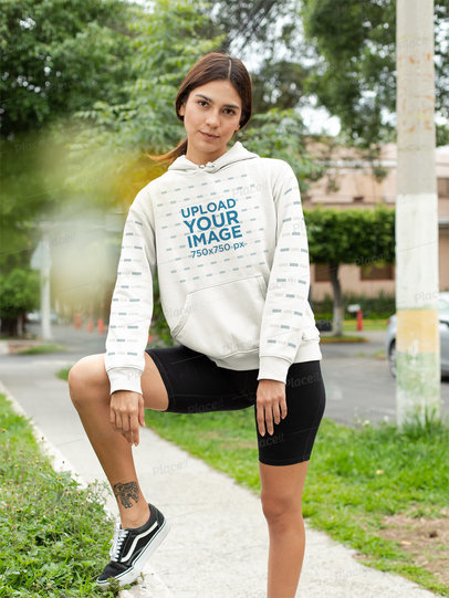 Pullover Hoodie Mockup with a Customizable Sleeve of a Woman by a Garden Street 28306