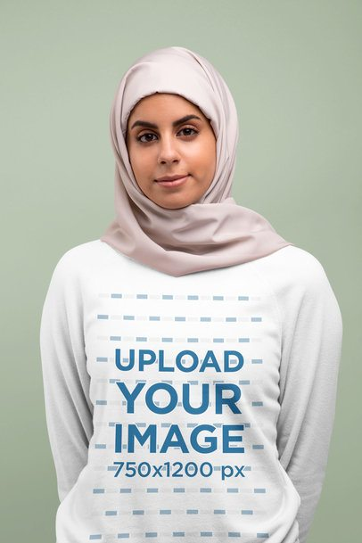 Crewneck Sweatshirt Mockup Featuring a Woman With a Hijab Against a Solid Color Backdrop 28275