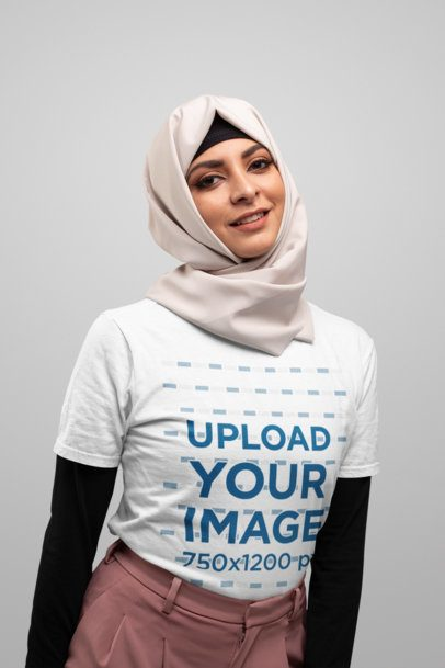 T-Shirt Mockup of a Woman Wearing a Hijab with a Plain Background 28287