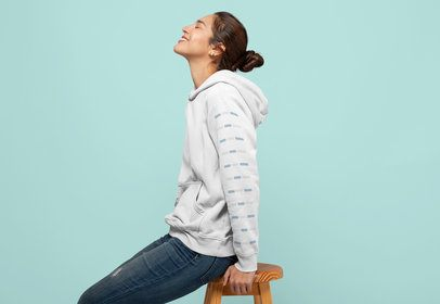 Mockup of a Woman Wearing a Pullover Hoodie Sitting on a Stool 28311
