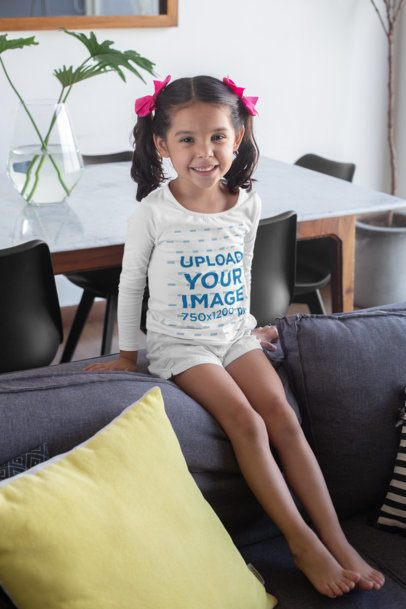 Long Sleeve T-Shirt Mockup of a Little Girl with Bows Sitting on a Couch 28094