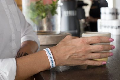 Wristband Mockup of a Woman at a Cafe 28216