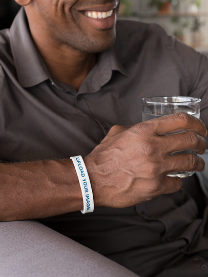Silicone Wristband Mockup Featuring a Man Holding a Glass of Water 28231