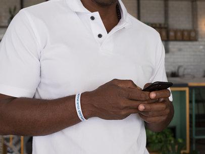 Wristband Mockup of a Man Looking at His Phone 28240