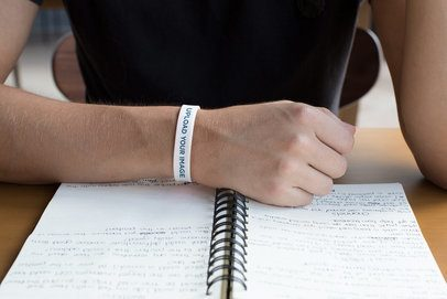 Silicone Wristband Mockup of a Man Looking at His Notes 28247
