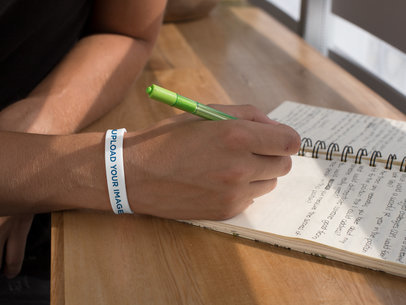 Silicone Wristband Mockup of a Man Writing down Notes 28245