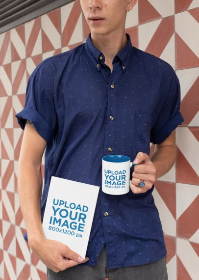 Mockup of a Blue Shirted Man Holding a Book and an 11 oz Mug with Inner Rim Color 28460