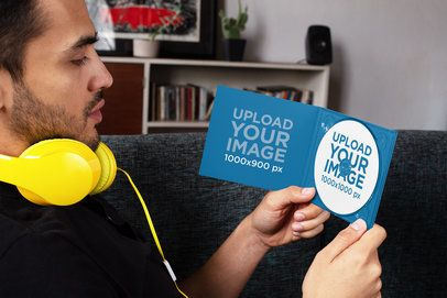 Mockup of a Man with Headphones Looking at a Digipak with a CD 28353