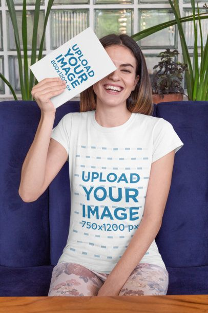 Mockup of a Joyful Woman Wearing a T-Shirt and Holding a Book in Front of Her Face 28490