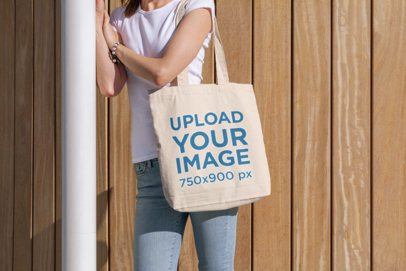 Tote Bag Mockup Featuring a Young Woman Standing by a Wooden Wall 196-el