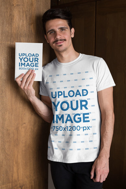 T-Shirt Mockup of a Man Holding a Book While Leaning on a Wooden Door 28499